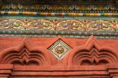 Mosaico colorido contra la pared roja Foto de archivo