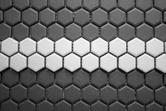Mosaico de las baldosas cerámicas hecho de Rhombus grises con una raya blanca en el centro, sin la mampostería, la malla-base y e imagen de archivo