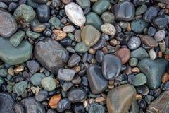 Mosaico de pedra molhado brilhante na praia Fotografia de Stock Royalty Free