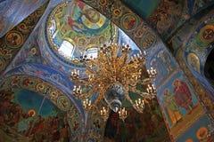 Mosaiker och en utsmyckad ljuskrona i inre av den kyrkliga nollan Arkivfoto