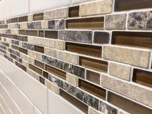 Mosaiska tegelplattor gjorde av exponeringsglas och stenen, nyligen installerat på väggen som garnering- eller kökbacksplash arkivbilder