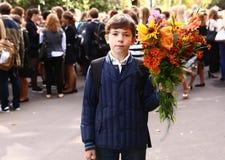 MOSCÚ, EL 1 DE SEPTIEMBRE DE 2015: El muchacho no identificado con las flores celebra el primer día escolar en el 1 de septiembre Fotos de archivo libres de regalías