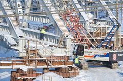 MOSCÚ, FEBRERO 01, 2018: Opinión sobre trabajadores con la grúa de la oruga que construye un puente del metal a través de pistas  Fotos de archivo libres de regalías