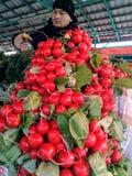Moscú, RF 26 de marzo de 2019: rábanos rojos frescos en el contador del mercado el vendedor irriga los verdes del espray foto de archivo
