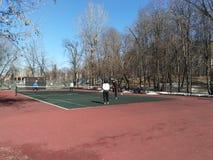 Mosc?, RF marzo, 31: las mujeres y los hombres juegan a tenis en la corte al aire libre en el parque de la ciudad foto de archivo