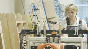 Moscú, Rusia - abril de 2019: Mujer que trabaja en la máquina de la carpintería acci?n Profesional de la mujer centrado en el tra fotos de archivo