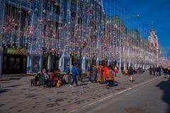 MOSCÚ, RUSIA ABRIL, 24, 2018: Gente en luces de una Navidad festivas en la calle de Nikolskaya con muchos tienda de souvenirs ade Imágenes de archivo libres de regalías