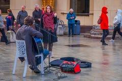 MOSCÚ, RUSIA ABRIL, 24, 2018: Opinión al aire libre el músico que toca una guitarra electrónica en la acera, con algunas personas Imagen de archivo libre de regalías