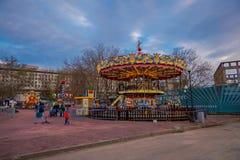 MOSCÚ, RUSIA ABRIL, 24, 2018: Opinión al aire libre gente con sus niños en un carrusel que disfrutan del tiempo libre con Imagen de archivo libre de regalías