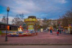 MOSCÚ, RUSIA ABRIL, 24, 2018: Opinión al aire libre gente con sus niños en un carrusel que disfrutan del tiempo libre con Fotografía de archivo libre de regalías