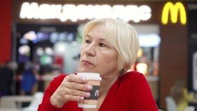 MOSCÚ, RUSIA CIRCA ENERO DE 2018: Café de consumición de la mujer mayor sedienta de la taza de papel en el ` s de McDonald en la  metrajes