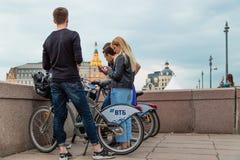 MOSCÚ, RUSIA - 30 DE ABRIL DE 2018: Un grupo de individuos y las muchachas se colocan con las bicicletas en el puente de Moskvore Fotografía de archivo