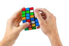 MOSCÚ, RUSIA - 31 de agosto de 2014: Rompecabezas del cubo del ` s de las manos y de Rubik Foto de archivo libre de regalías