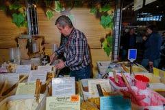Moscú, Rusia - 25 de febrero de 2017: El vendedor canoso del hombre en la feria llena un tarro de la miel para el comprador Fotos de archivo libres de regalías