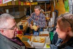 Moscú, Rusia - 25 de febrero de 2017: El vendedor canoso del hombre en la feria llena un tarro de la miel para los compradores Imágenes de archivo libres de regalías