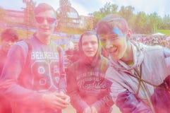Moscú, Rusia - 3 de junio de 2017: Agrupe el retrato alegre de la sonrisa tres adolescentes en nube del polvo rosado en Holi Imagen de archivo libre de regalías