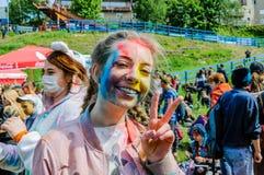 Moscú, Rusia - 3 de junio de 2017: El adolescente con los apoyos y las coletas, en pintura multicolora, muestra un gesto de la vi Imagenes de archivo