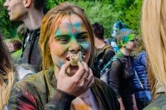 Moscú, Rusia - 3 de junio de 2017: La chica joven con la cara multicolora, manchada con la pintura en Holi, muerde el helado en g Fotografía de archivo libre de regalías