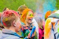 Moscú, Rusia - 3 de junio de 2017: Muchacha pelirroja de risa feliz en el epicentro de un chapoteo colorido en el festival de Hol Fotos de archivo