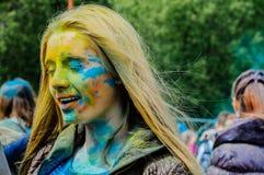 Moscú, Rusia - 3 de junio de 2017: Retrato de la muchacha rubia joven, diversos colores pulverizados en el festival Holi de las p Imagenes de archivo