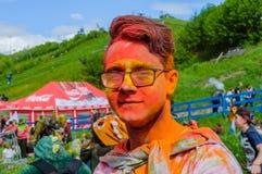 Moscú, Rusia - 3 de junio de 2017: Retrato del inconformista-muchacho joven en vidrios después de un headshot colorido en el fest Foto de archivo