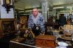 Moscú, Rusia - 19 de marzo de 2017: El vendedor del vintage adornó rico los relojes de la chimenea de la colección en un mercado  Foto de archivo libre de regalías
