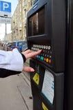 Moscú, Rusia - 14 de marzo de 2016 La mano de la mujer incorpora los datos a máquina del pago del estacionamiento Fotos de archivo libres de regalías