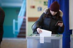 MOSCÚ, RUSIA - 18 DE MARZO DE 2018: El votante cae el boletín en Foto de archivo libre de regalías