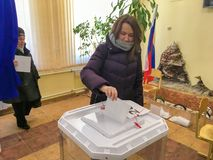 Moscú, Rusia - 18 de marzo de 2018: El votante pone la votación en la caja en las elecciones del presidente Imagen de archivo