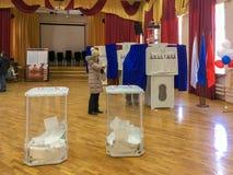 Moscú, Rusia - 18 de marzo de 2018: El votante pone la votación en la caja en las elecciones del presidente Fotos de archivo