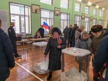 Moscú, Rusia - 18 de marzo de 2018: El votante pone la votación en la caja en las elecciones del presidente Imagenes de archivo