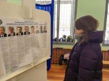 Moscú, Rusia - 18 de marzo de 2018: Los votantes examinan la lista en las elecciones del presidente Imágenes de archivo libres de regalías