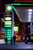 MOSCÚ, RUSIA - 20 DE MARZO DE 2018: Un hombre con dos niños camina más allá de BP conecta la gasolinera en la carretera en una Mo Imagen de archivo libre de regalías