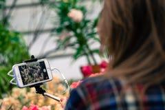 MOSCÚ, RUSIA - 12 DE MARZO DE 2018: Un visitante hace las fotos de flores en el teléfono en un uno mismo-palillo en el Aptekarsky Imágenes de archivo libres de regalías