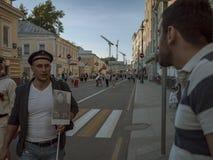 MOSCÚ, RUSIA - 9 DE MAYO DE 2016: Atleta en un casquillo sin hablar con un amigo alrededor de la calle después del regimiento del Foto de archivo libre de regalías