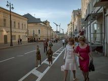 MOSCÚ, RUSIA - 9 DE MAYO DE 2016: Dos niñas en ropa histórica militar y dos mujeres en trajes de negocios están caminando Imagen de archivo libre de regalías