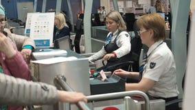 Moscú, Rusia - 6 de mayo de 2019: Dos personales de seguridad aeroportuaria femeninos que comprueban la identificación en un enre metrajes
