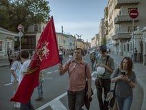 MOSCÚ, RUSIA - 9 DE MAYO DE 2016: El hombre con una bandera roja y la familia están caminando a lo largo de la calle después del  Foto de archivo libre de regalías
