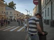 MOSCÚ, RUSIA - 9 DE MAYO DE 2016: Un hombre en un polo rayado pone hacia fuera un cigarrillo al borde de una urna alrededor de la Foto de archivo