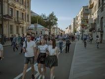 MOSCÚ, RUSIA - 9 DE MAYO DE 2016: Una cabeza rapada con dos muchachas está caminando a lo largo de la calle después del regimient Imágenes de archivo libres de regalías