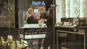 Moscú, Rusia - 16 de septiembre de 2018: Perfume del olor el oler de la mujer con su hasbent en la tienda de la belleza Una mucha metrajes
