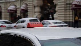 MOSCÚ, RUSIA - DICIEMBRE: Ciérrese para arriba de muestra anaranjada del tejado del taxi con los inspectores en el fondo de coche metrajes