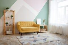 Mosc?, Rusia, el 7 de abril de 2019: Sala de estar agradable con el sof?, alfombra, planta verde en un estante para libros fotografía de archivo libre de regalías