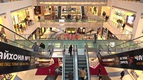 MOSCÚ, RUSIA - FEBRERO, 28, 2017 Escaleras móviles y tiendas de la metrópoli moderna de la alameda de compras imagenes de archivo