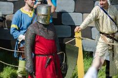MOSCÚ, Rusia-junio 06,2016: El guerrero medieval se prepara para el duelo El caballero se coloca en casco con la espada y el escu Fotografía de archivo