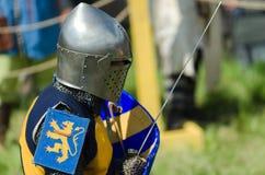 MOSCÚ, Rusia-junio 06,2016: El guerrero medieval se prepara para el duelo El caballero se coloca en casco con la espada y el escu Fotos de archivo libres de regalías
