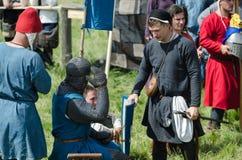 MOSCÚ, Rusia-junio 06,2016: El guerrero medieval se prepara para el duelo El compañero del caballero viste el casco antes de duel Foto de archivo