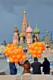 Moscú, Rusia, marzo, 20, 2016, escena rusa: gente con los globos anaranjados delante de la catedral de la albahaca del St en Mosc Fotografía de archivo