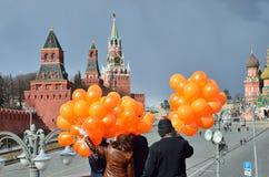 Moscú, Rusia, marzo, 20, 2016, escena rusa: gente con los globos anaranjados delante de la catedral de la albahaca del St en Mosc Foto de archivo libre de regalías