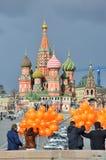 Moscú, Rusia, marzo, 20, 2016, escena rusa: gente con los globos anaranjados delante de la catedral del ` s de la albahaca del St Fotos de archivo libres de regalías
